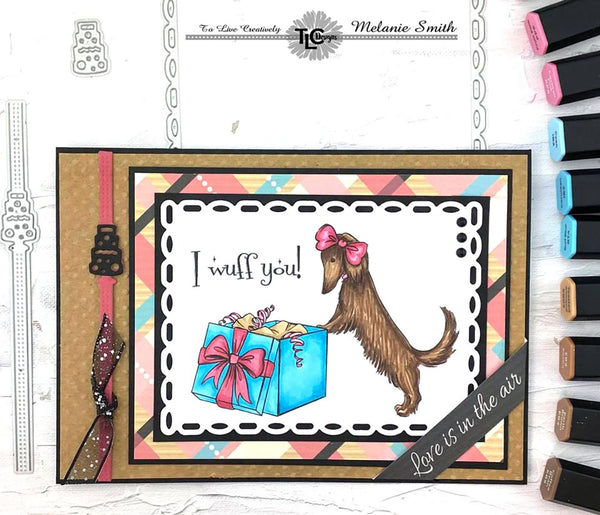 It's a delightful day for the Posh Pups polymer stamps from TLCDesigns.shop in this greeting card!  The long haired Doxi is opening her present and Love is in the air!  The Garden Rectangle die and the Celebrate Ribbon die are the perfect accents for this card!