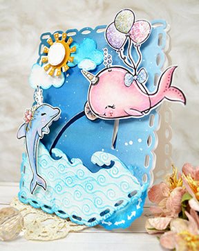 It's an ocean scene with the Fancy Fin digital stamp illustrations from TLCDesigns.shop created to move interactively on the card project with the Double Dial Die 1 product. It's a floating pink whale!