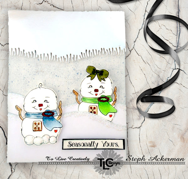 Two little snow babies sitting on a hill!  The greeting card says Seasonally yours, and is simply a delightful project that includes a twist on the use of the grassy die from TLCDesigns.shop.  Turn the paper cut upside down on silver paper and it turns into a delightful icicle display!  Simple and fun Holiday greeting cards!