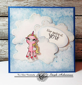 Beautiful and puffy looking clouds designed from the Cherry On Top Die set from TLCDesigns.shop on this pretty in sky blue greeting card. The Alicorn stamped image colored in pink is Star gazing at YOU! as the sentiment says!