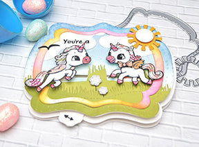 The Alicorn Happiness stamps from TLCDesigns.shop used with the Interactive die called See You In The Center designed with sweet pink and blue spring and Easter colors! The little field scene is the perfect backdrop for these adorable images