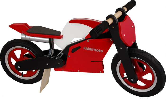 A photo of our Red Superbike, with wooden spinning handlebars, a motorbike styled seat, wooden exhaust pipes, and motorbike-styled rims