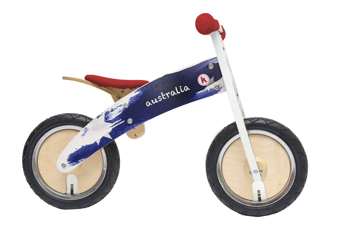 "Our Australian Kurve has a red seat and handlebars, a white base, and blue paint strokes on the main frame. The side of the frame reads ""Australia"" in white chalk-like text"