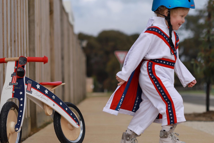 A photo of a young boy with a Metallic Ocean Blue helmet on and an Evel Knievel jumpsuit, walking away from our Evel Knievel Kurve