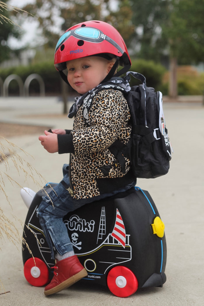 A photo of a young boy wearing our Skull & Bones mini backpack with a Red Goggle helmet. He is wearing a leopard print jacket and sitting on a suitcase outside an airport