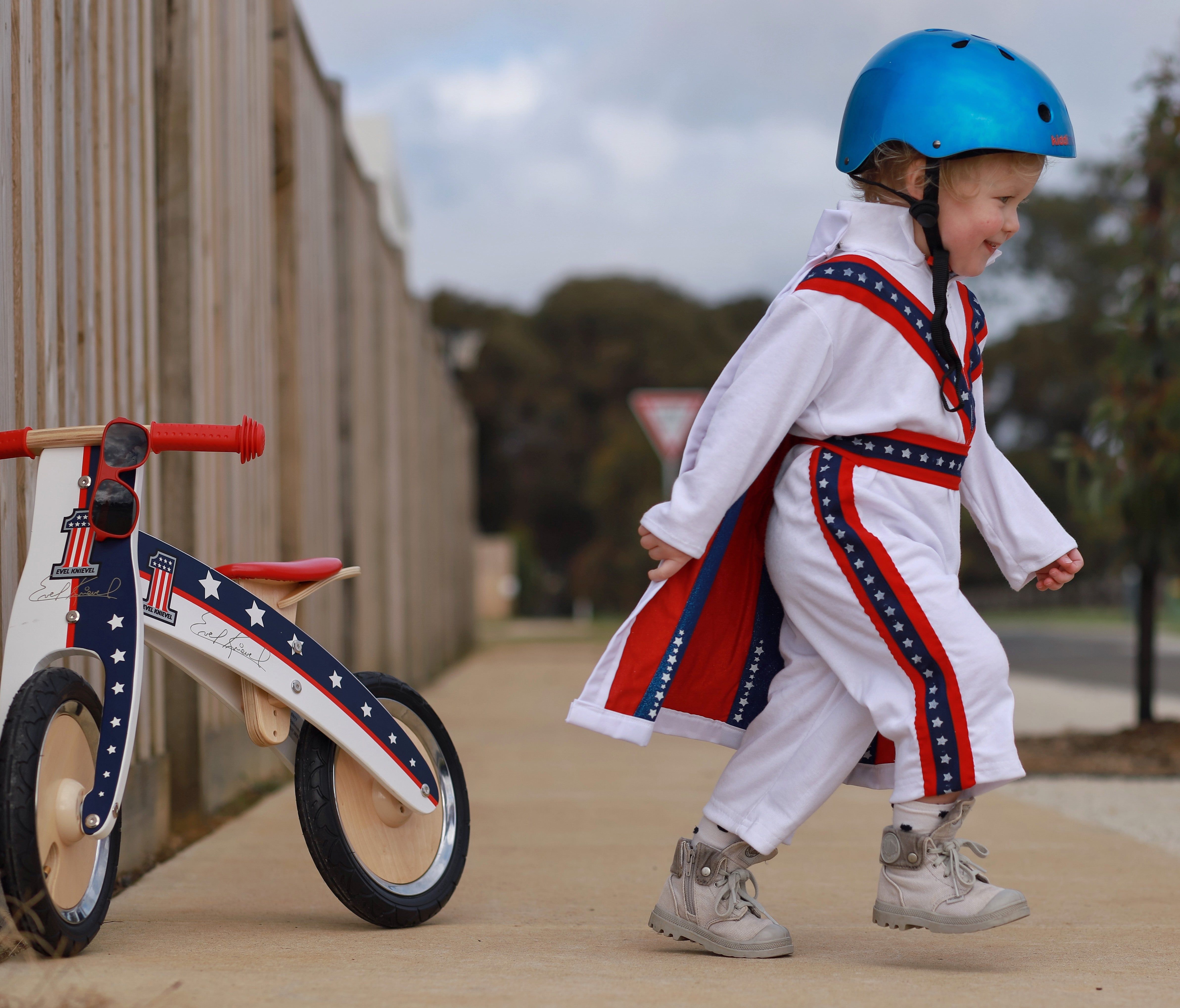 A photo of a boy in our Metallic Ocean Blue helmet walking away from his Evel Knievel Kurve