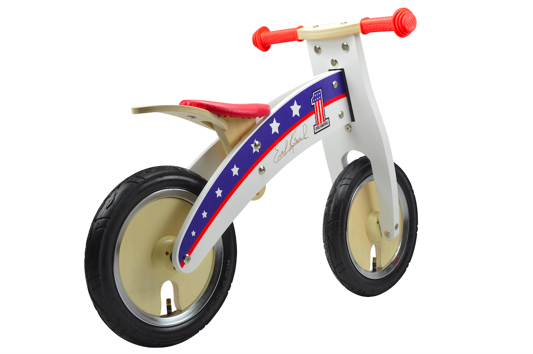 A photo of our Evel Knievel Kurve, featuring a red seat and handlebars, and natural timber wheels