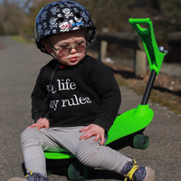 A photo of a young boy wearing our Skull & Bones helmet in a park. He is sitting on a bright green skateboard, and wearing sunglasses and a black sweater