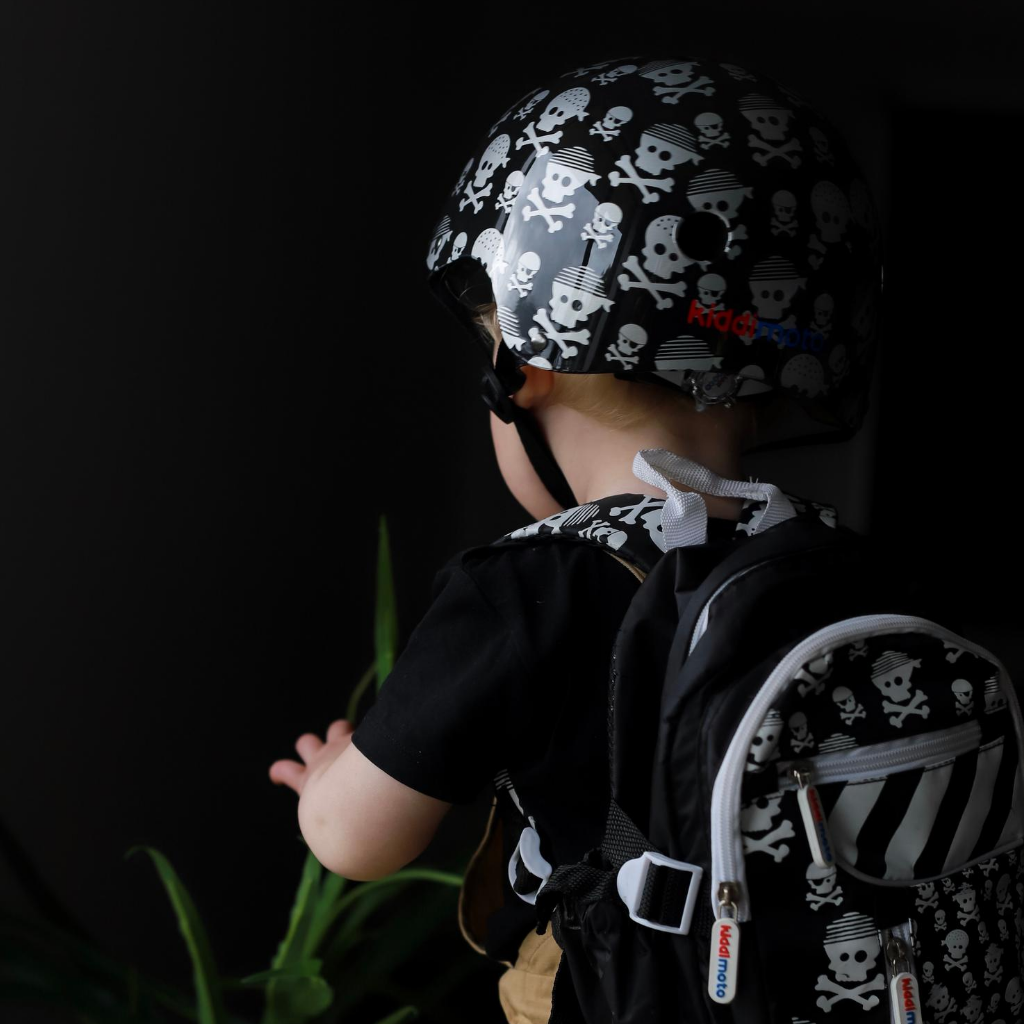A photo of a young boy facing away from the camera, showing off the back of his Skull & Bones helmet and the matching Skull & Bones mini backpack