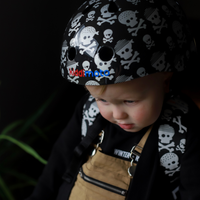 A young boy wearing our Skull & Bones helmet and the matching Skull & Bones mini backpack. He is wearing a black sweater and tan overalls, in front of a black background