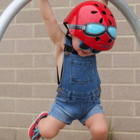 A photo of a young boy wearing denim overalls, sunglasses, and our Red Goggle helmet. He is hanging from a short metal pole with a big smile on his face!