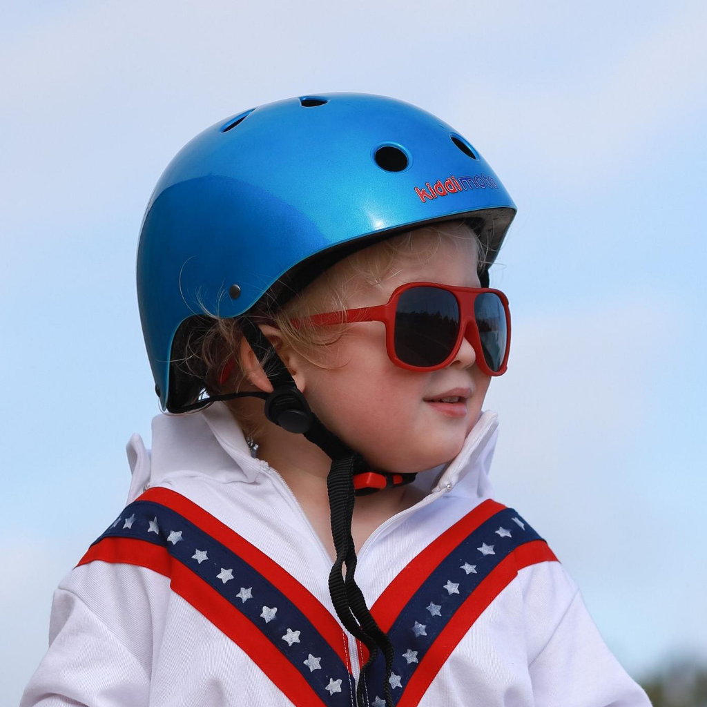 A photo of a boy in a Evel Knievel jumpsuit and red sunglasses wearing our Metallic Ocean Blue helmet