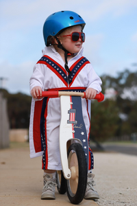 A photo of a young boy with a Metallic Ocean Blue helmet and a pair of red sunglasses on, riding around with his Evel Knievel Kurve and a matching jumpsuit on