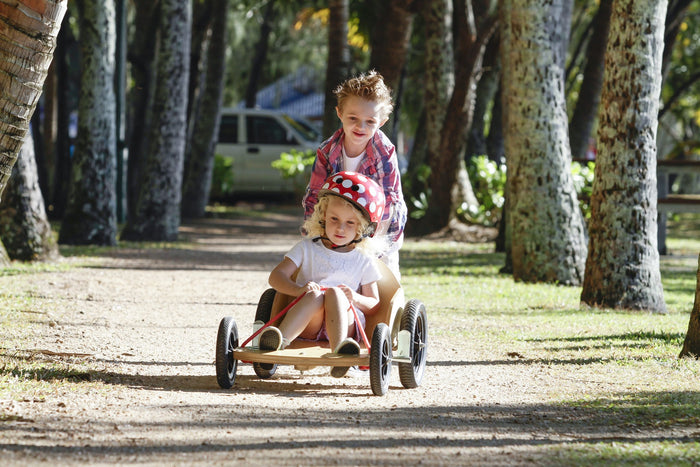 A blonde boy pushing along a blonde girl with a Red Dotty helmet on their billy kart