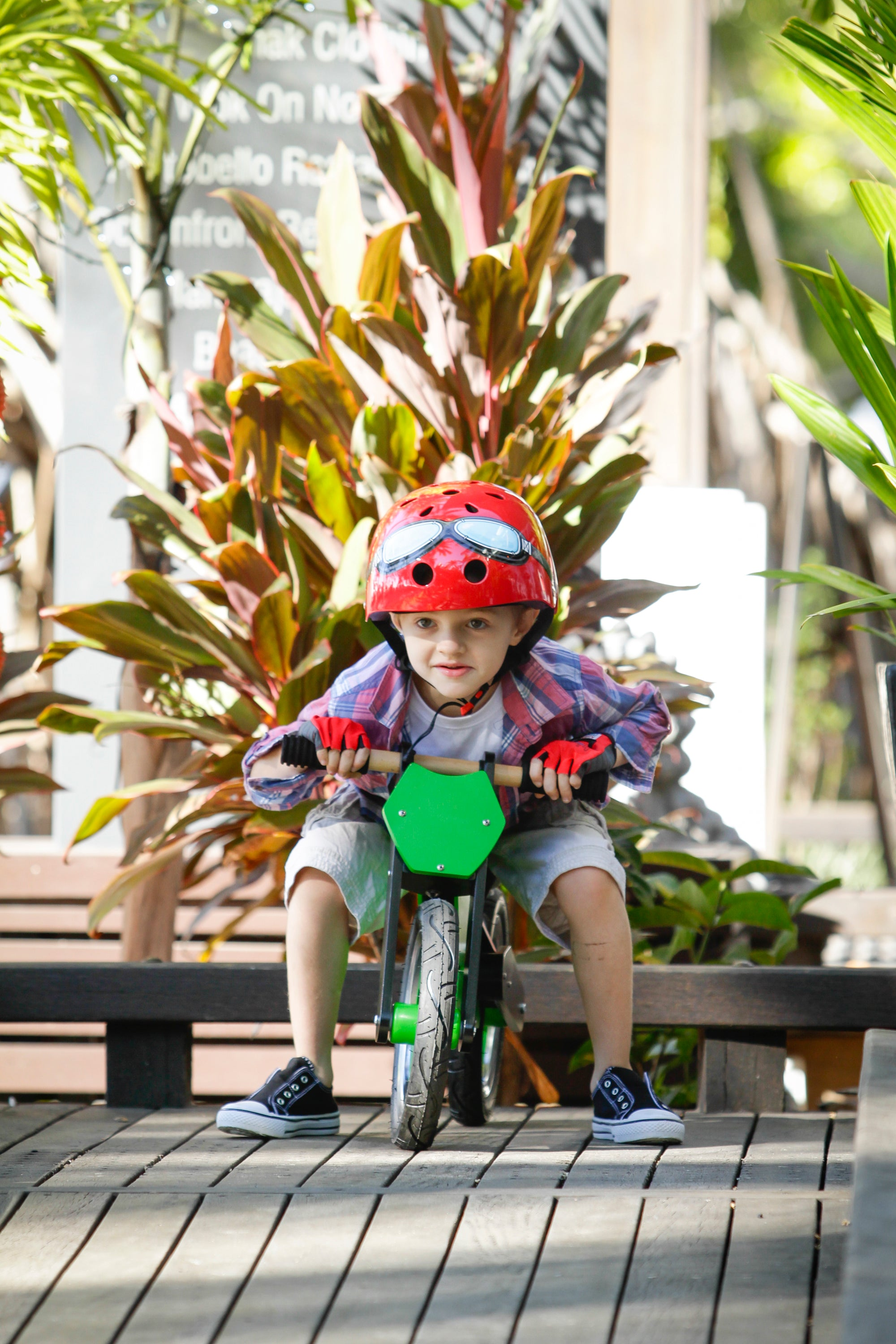 A photo of a young boy wearing a Red Goggle helmet and a pair of Red Kiddimoto Gloves on a Green Superbike. He looks like he is preparing himself to ride down a dip