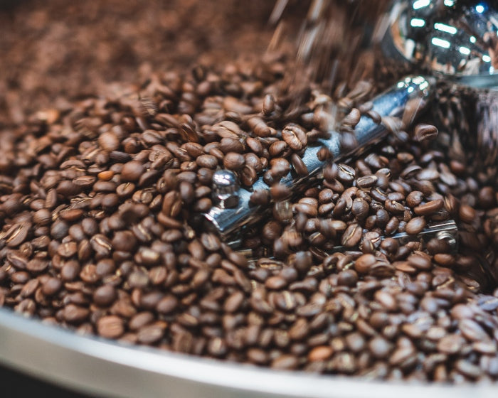 Whole beans falling into Giessen roasting machine before sale