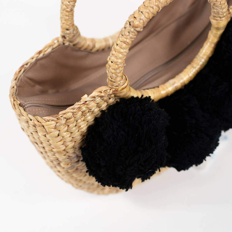 straw hand bag with black pom poms