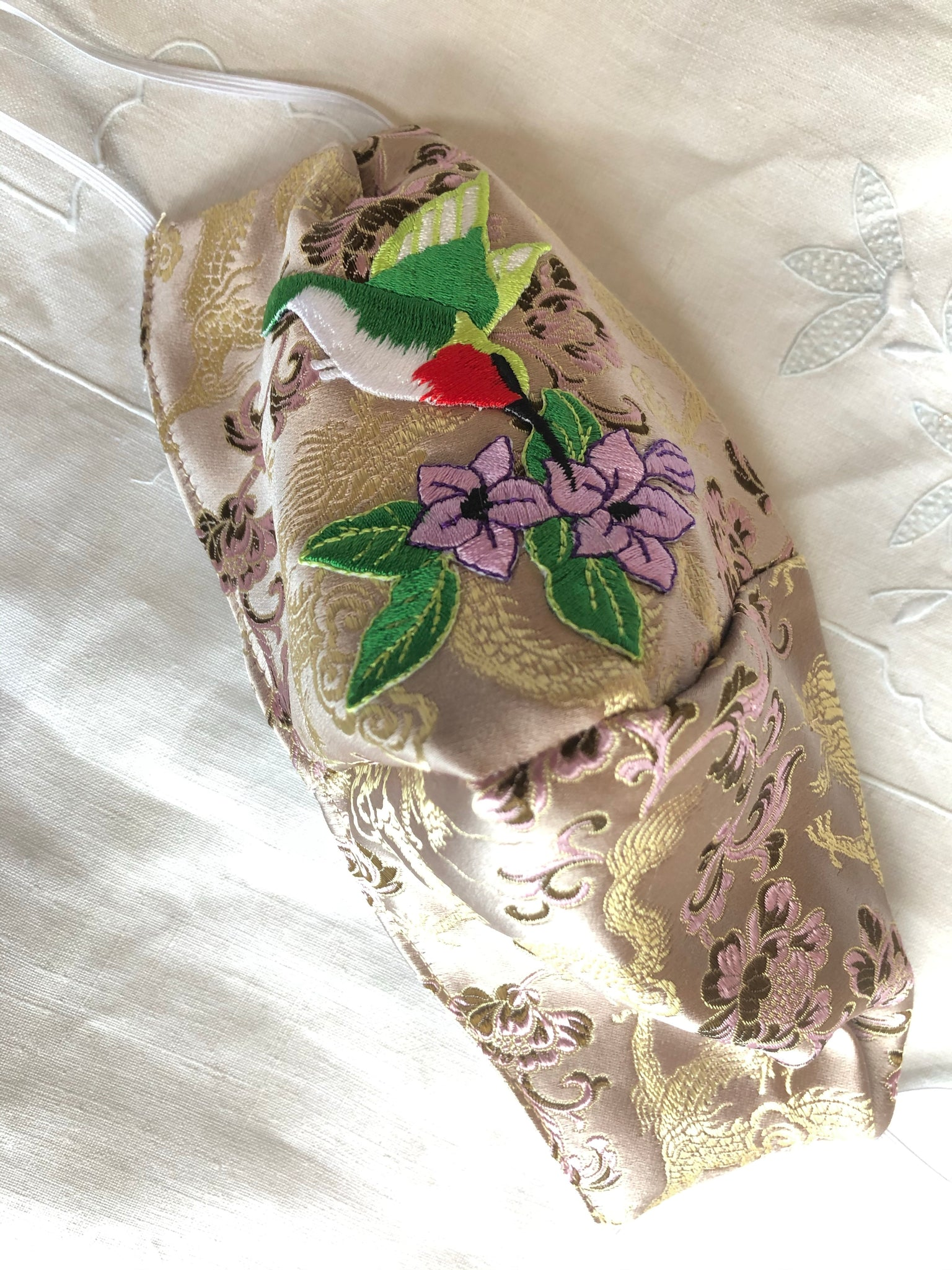 Beige silky hummingbird with purple flowers