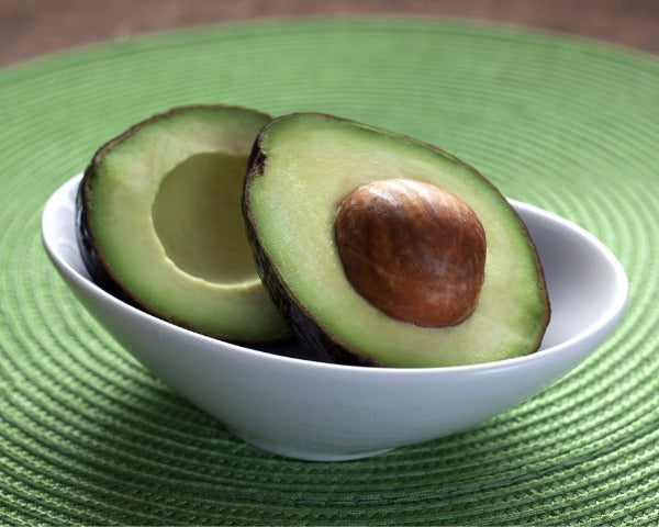 Avocado halves in a bowl