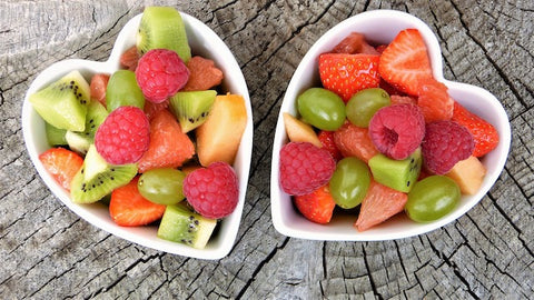 Two heart-shaped bowls of berries and grapes
