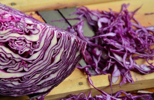 Partially sliced red cabbage on a cutting board