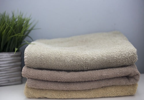 Stack of earthy colored towels by a small succulent plant