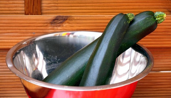 Two zucchinis in red metal bowl