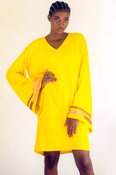 Yellow Kaftan with strips of African print wax on an exaggerated sleeve. It is so easy to throw one on and get on with the day
