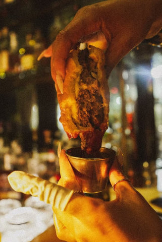 Cheeseburger being held and dipped into ketchup in a bar setting