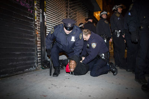 Police officers arrest a demonstrator Wednesday. Law enforcement fears more violent protests when the teen is buried. (The Associated Press)