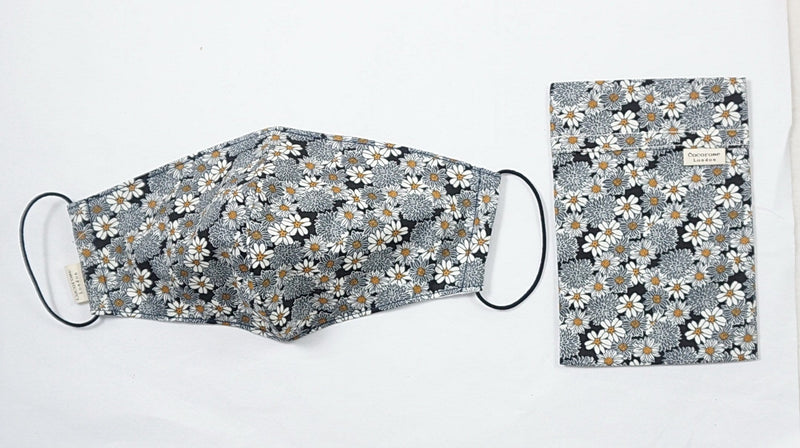 the best facemask and face covering with filter pockets and pretty black and grey daisy flower print. With a matching storage bag pouch.