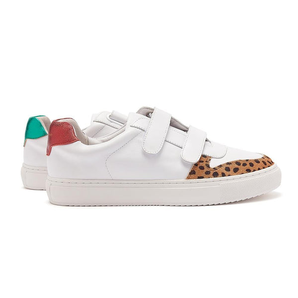 Double velcro strapped, low top white leather trainers with leopard print and mismatched, metallic red and green back tabs