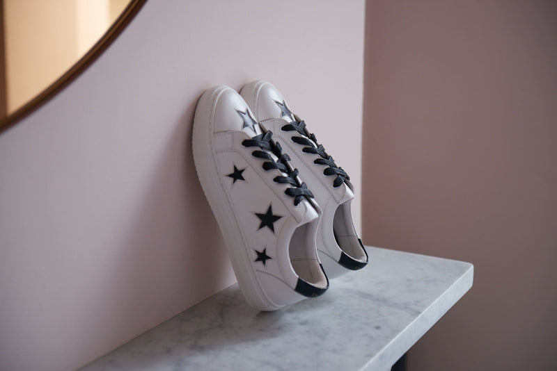 On trend and comfortable designer white trainers with black stars