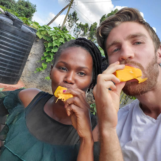 Woman and man eat fresh mango