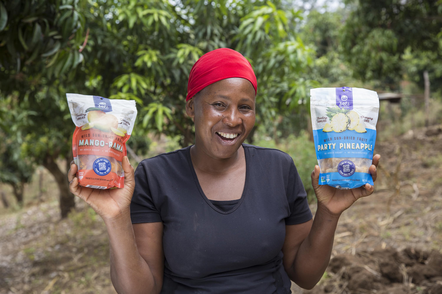 African woman holding bags of Jali Fruit Co. dried fruit