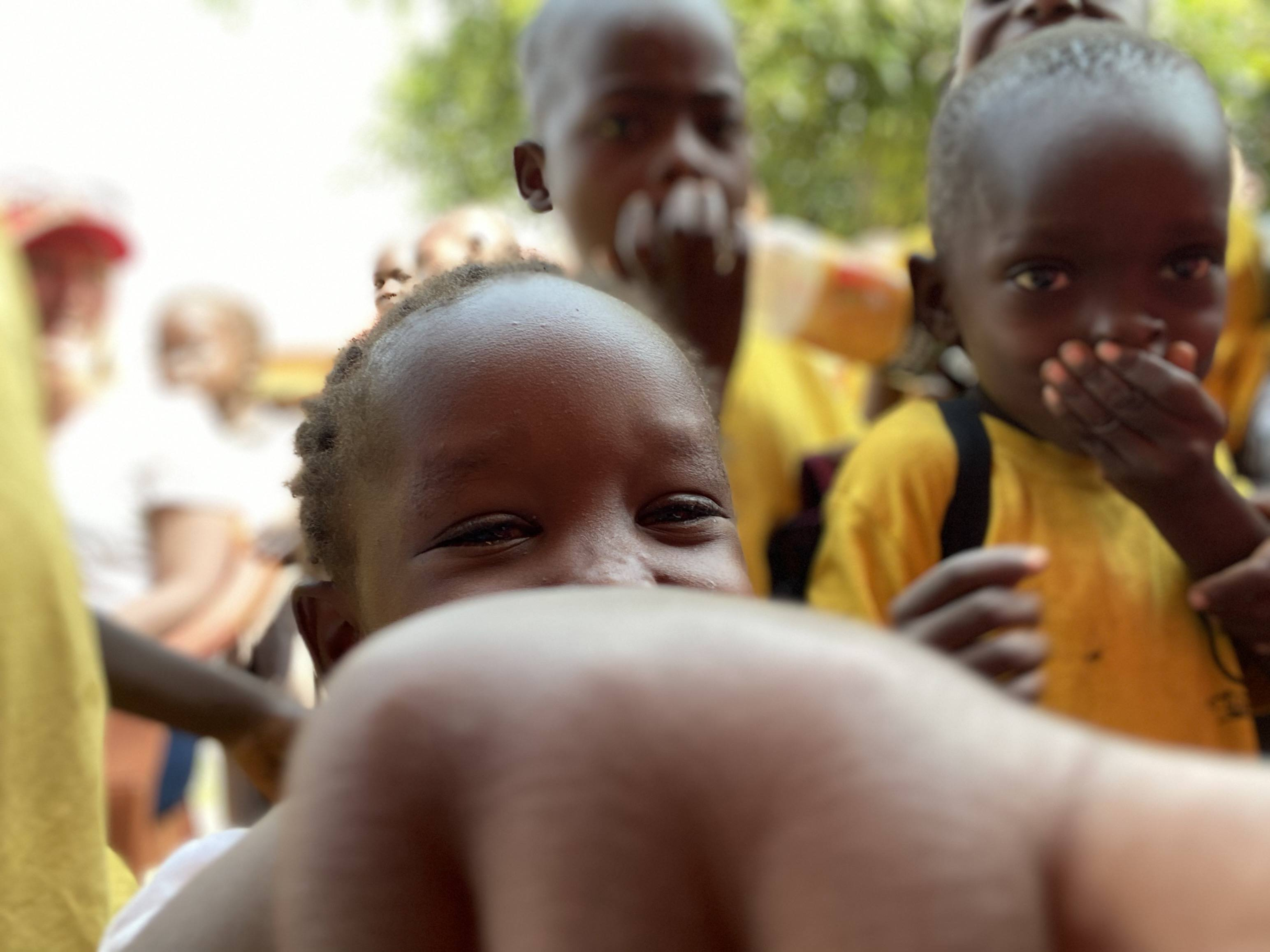 East African school children pointing at the camera