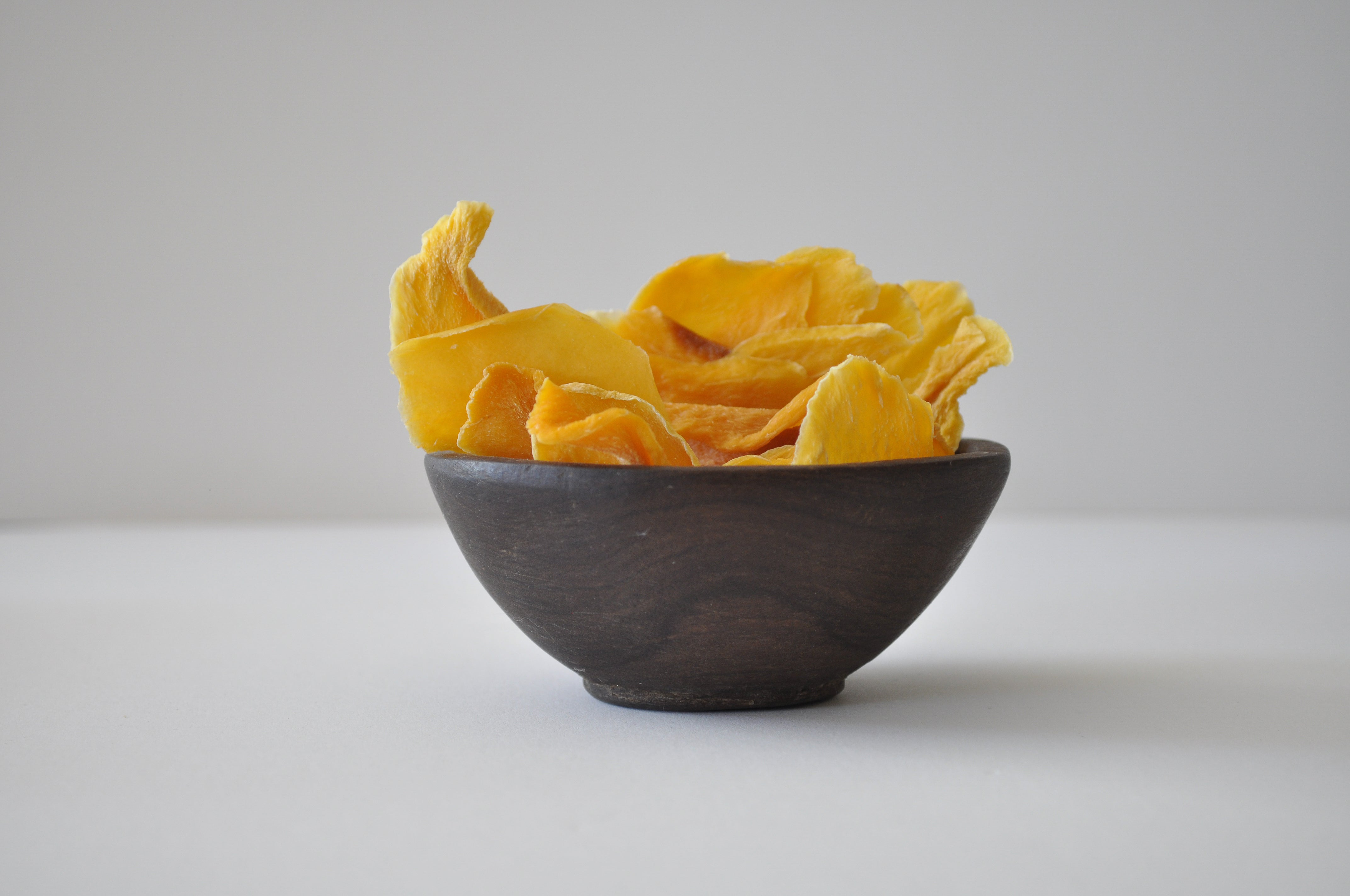 Slices of dried mango in a wooden bowl on a white countertop