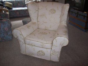 Wing chair with piping and no skirt.