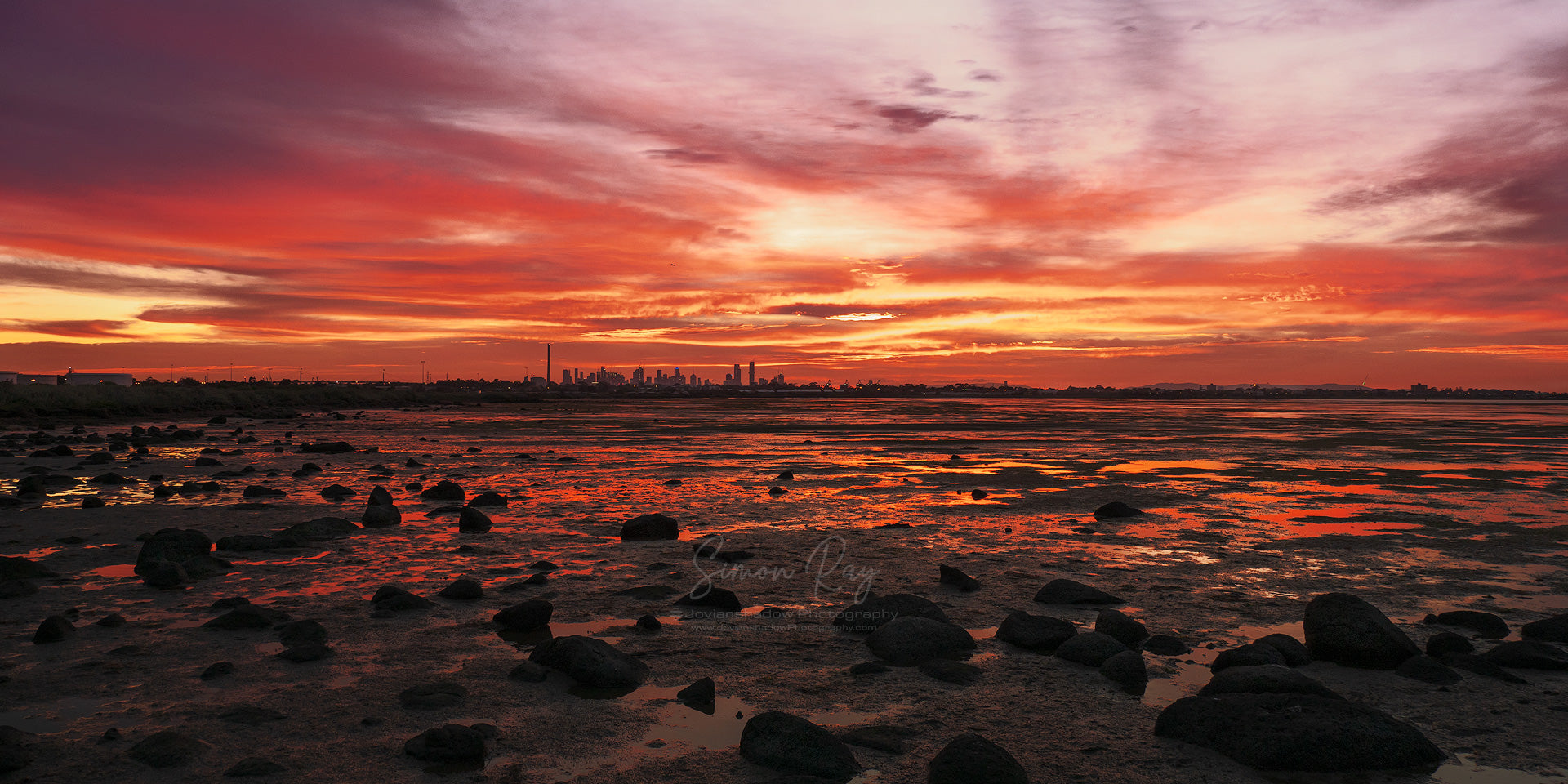 Fiery red sunrise over the Melbourne skyline during low tide at Altona Dog Beach. Australian Landscape Photography.