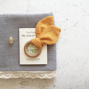 Bunny Ears Baby Teether in Saffron made from organic cotton muslin and natural beechwood. Relieve the pain of your babies teething naturally.