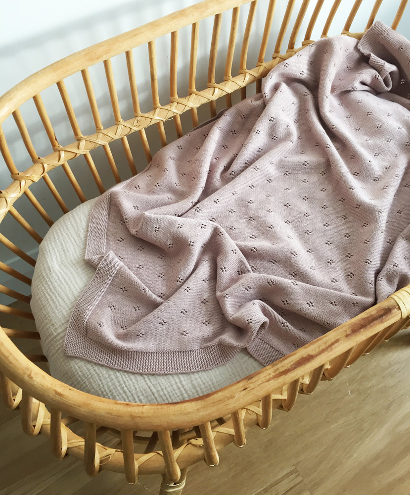 organic cotton knitted baby blanket in dusk in bassinet
