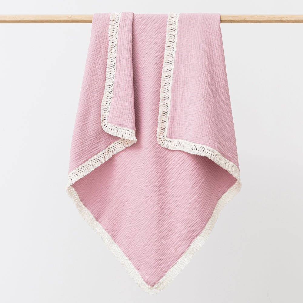 Organic cotton muslin baby blanket with tassel fringe in peony pink