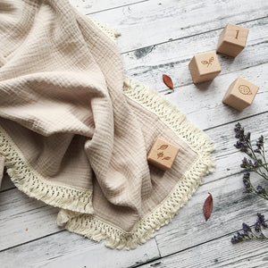 Organic cotton muslin baby blanket with tassel fringe in sand