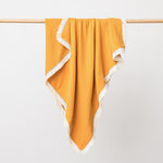 Organic cotton muslin baby blanket with lace trim in saffron