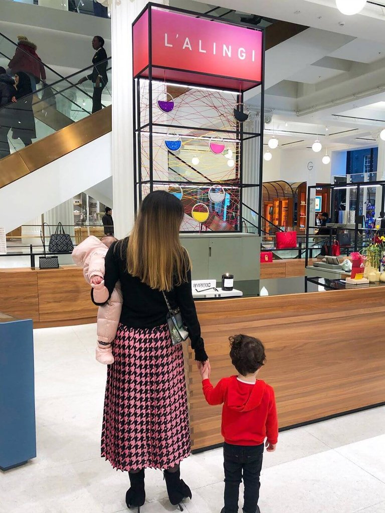Alia Zaki Alia with children at the Selfridges store in London. L'alingi display, with clutches, on the backgound