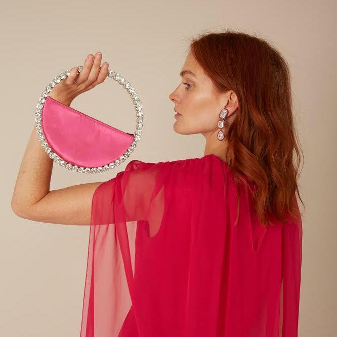 Model holding a L'alingi pink satin round clutch with with crystal encrusted handle
