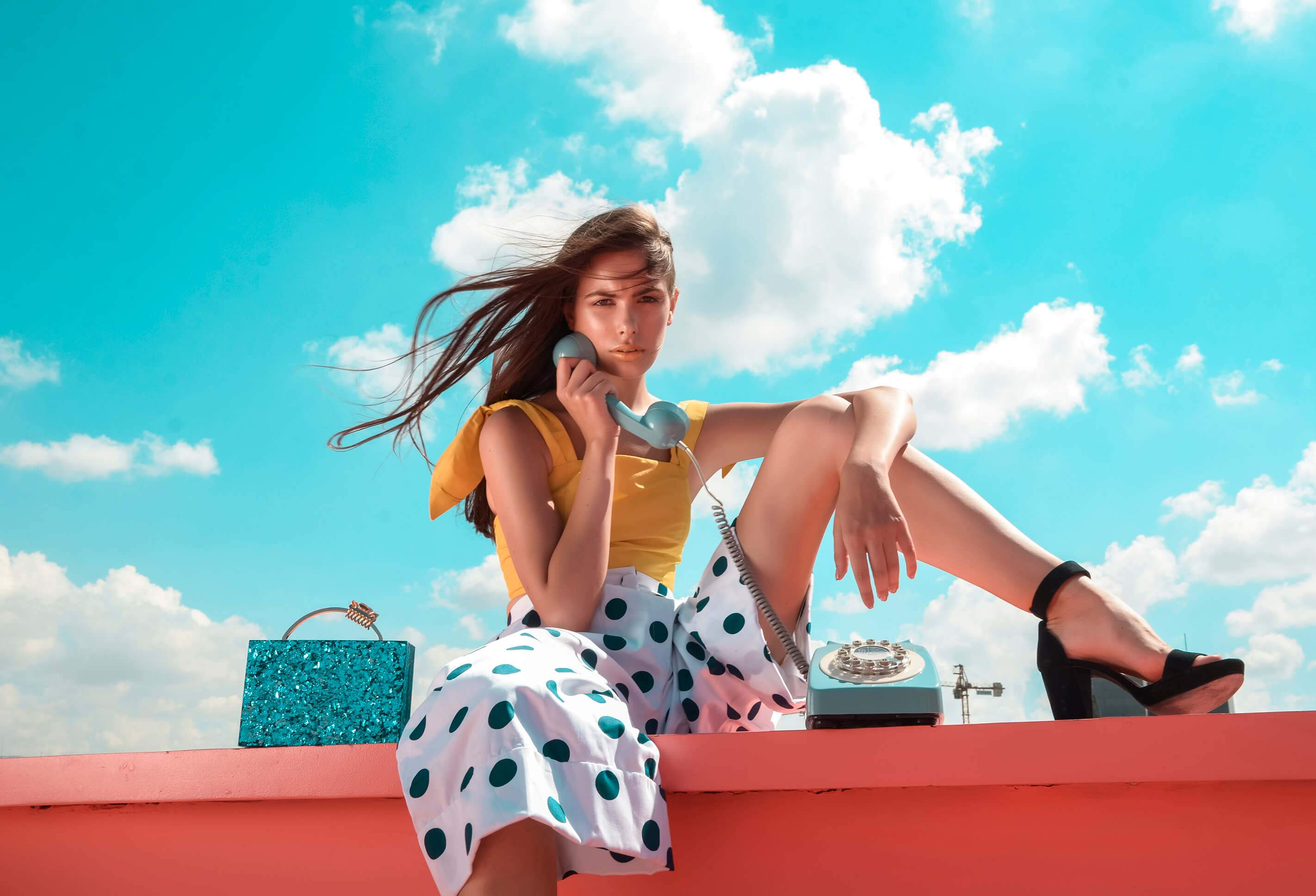 L'alingi London Spring-Summer 2019 Lookbook cover with a model holding a classic blue phone with a blue halana box clutch on the side
