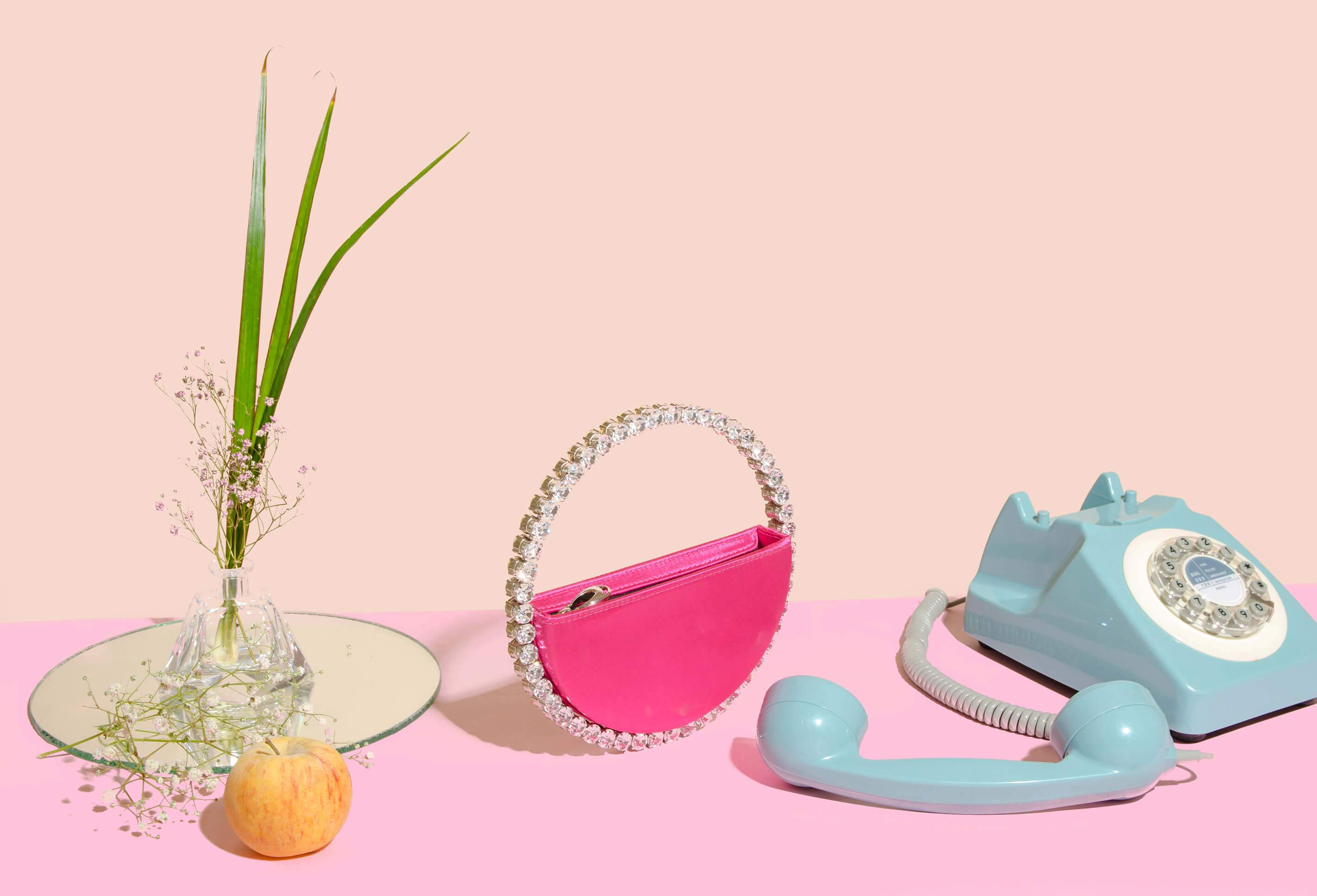 L'alingi London Spring-Summer 2020 Lookbook cover with Pink eternity evening clutch, a blue telephone, an apple and some plants