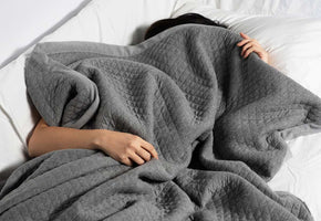 a person lying down, covered by the curfew dream blanket with her left hand and right arm uncovered