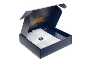 and angled image of the curfew dream blanket box opened, showing the folded blanket wrapped in tissue paper, and the free nightly salve on the right side insert